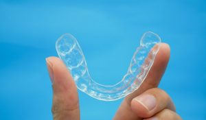 Hand Holding Clear Plastic Retainer Teeth That Isolated On Blue Sky Background. It's An Equipment For Orthodontist Give The Patient To Orthodontic Surgery In Dental Clinic Or Hospital